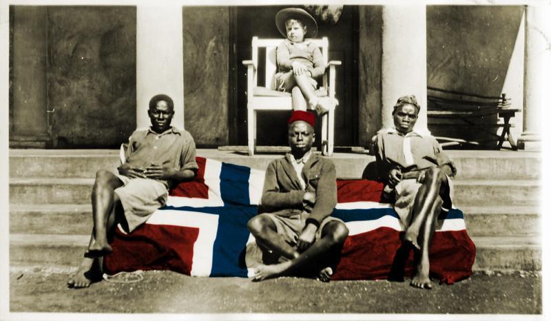 Kolorert bilde. Et norsk flagg er brettet ut over en trapp til en balkong, tre afrikanere sitter på flagget. En lys gutt sitter på en stol på balkongen. (Foto/Photo)