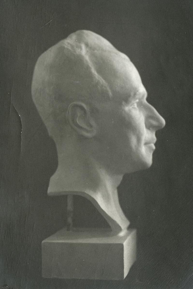 Byst föreställande Pehr Engwall, av John Runer 1921. Bysten är monterad på gipsplatta och under denna ett handskrivet papper.