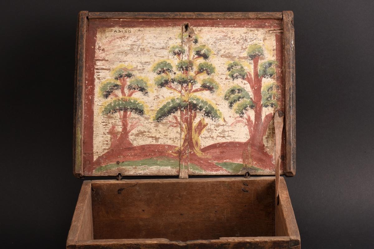Rektangulärt skrin med plant lock av ek. Sliten bemåning i form av blommor i rött, grönt och gult mot rödfärgad botten. På insidan av locket är tre stiliserade träd målade på mot vit botten och där finns också flera olika påskrifter, svårlästa.
