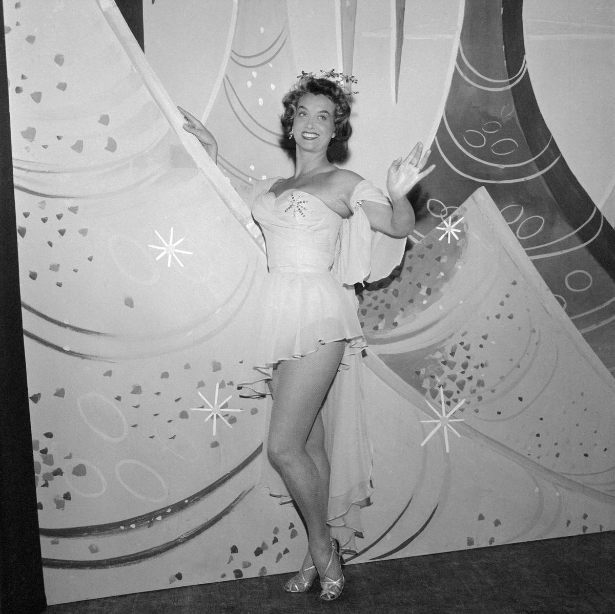 """Från debuten 1936 kom revy- och operettsångerskan Ester Estéry att medverka i ett otal uppsättningar vid teatern och turnerande revysällskap. Bakom artistnamnet döljer sig dopnamnen Ester Svensson och vidare Bergström efter hennes giftemål med kuplettförfattaren Tor Bergström (signaturen """"Herr Dardanell""""). Här ses hon i uppsättningen av 1959 års Klangerevy, """"Fortfarande folket"""", under premiären i Mjölby folkpark den 23 maj."""