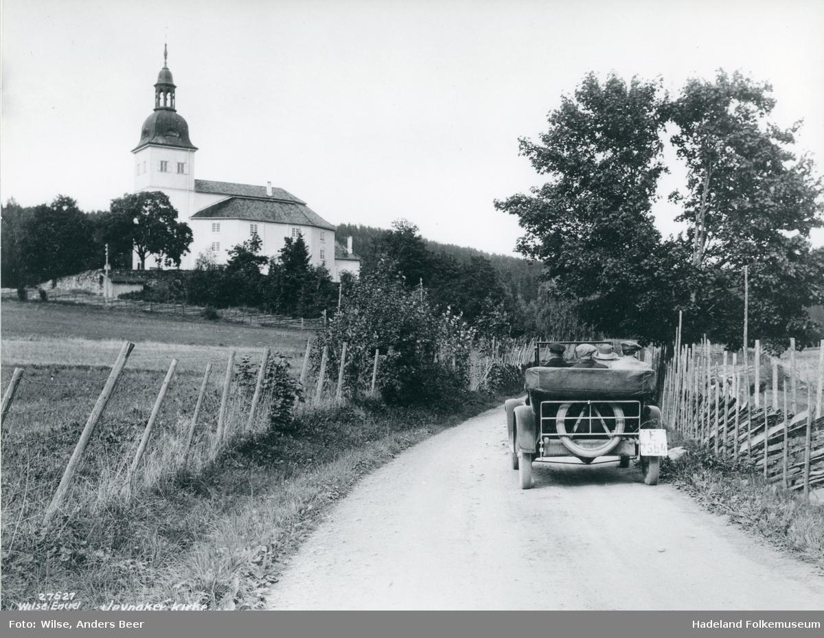 Jevnaker kirke. Åpen bil på veien nedenfor kirken.