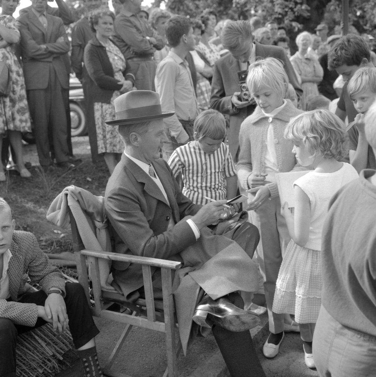 Paus i inspelningen av den romantiska komedin Lustgården i Vadstena 1961. På bilden kopplar Gunnar Björnstrand av från sin roll som adjunkt David Samuel Franzén för en stunds vila och autografskrivning.