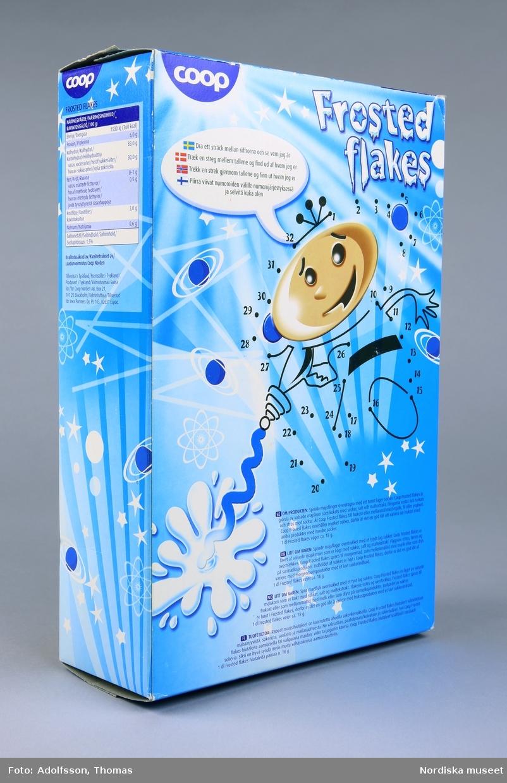 """Rektangulär flingförpackning av kartong med heltäckande färgillustrationer. Framsidan upptas av en rymdfigur och texten """"Frosted flakes cornflakes med överdrag av socker 500g"""". Baksidan utgörs av ritpyssel där streck kan dras mellan ett trettital punkter för att en figur ska framträda, enligt instruktion: """"Dra ett sträck mellan siffrorna och se vem jag är"""". På förpackningens kortsidor finns produktinformation. Se länkad fil."""