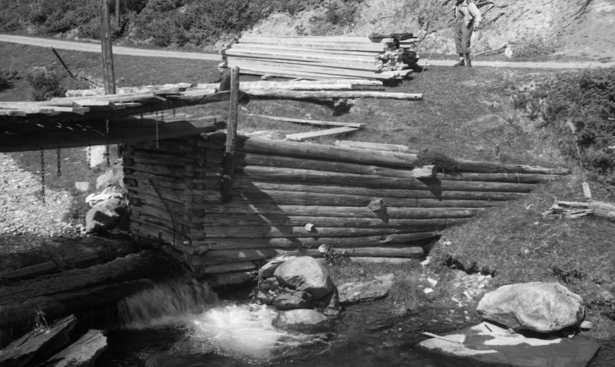 """Detalj fra fløtingsdam i elva Fåa i Tynset.  Fotografiet er tatt mot en tømmerkistekonstruksjon som danner damarm.  Overflata på denne damarmen er begrodd med grastorv og antakelig fylt ned masse fra en bakenforliggende grusrygg.  Til venstre for dammen aner vi hvordan vannet føres over ei """"golving"""", antakelig av tre, før det faller ned i en nedenforliggende kulp.  Dammen har bru av tre.  På tvers av denne brua er det lagt en god del plank - såkalte """"nåler"""" - som i fløtingssesongen ble stukket mot strømmen slik at de ble stående tett i tett med endene mot en horisontal svill ved damgolvingas øverkant og mot dambruas øverkant.  I enden av nålene henger nålekjettingen som ble brukt til å trekke opp nålene med når dammen skulle åpnes.  Da fotografiet ble tatt lå det en betydelig materialhaug innerst på damarmen, der en kjøreveg oppover dalen passerer.  Ved denne materialhaugen står det en mann.  Ettersom tømmerkistedammen later til å være i ferd med å rotne og rase ut, er det naturlig å tenke seg at dette kan være materialer som er brakt dit med sikte på fornyelse av dammen.  Dette fotografiet er ett av mange i en serie som ble tatt ved dammern i Fåa sommeren 1944, jfr. SJF. 1990-00222 - SJF. 1990. 00229."""