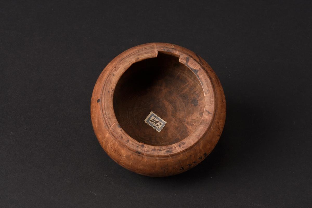 Rund svarvad smörask med lock, tillverad av trä. Locket har ett runt svarvat knopphandtag. Under asken finns det inskurna initialer, AIS.