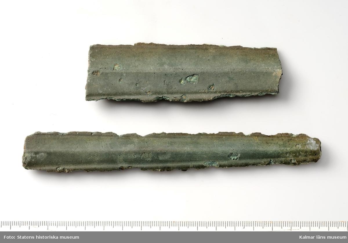 KLM 4861. Svärd, av brons. Rikt dekorerat fäste samt bit av klingan, klingan avbruten på flera ställen.  :1. Svärdsfäste, gjutet, dekorerat av koncentriska kretsar och spiraler. I fästet sitter en bit av svärdsklingan, sannolikt samma som nedanstående fragment.  :2. Svärdsklingan, två delar, delarnas längd 16,1 cm, bredd 3,4 cm, respektive längd 10,7 cm, bredd 2,3 cm. (Beskrivning under :1-:2 hämtad från ursprunglig utlånshandling och inte direkt från föremålen, författad av låntagaren SHM.)