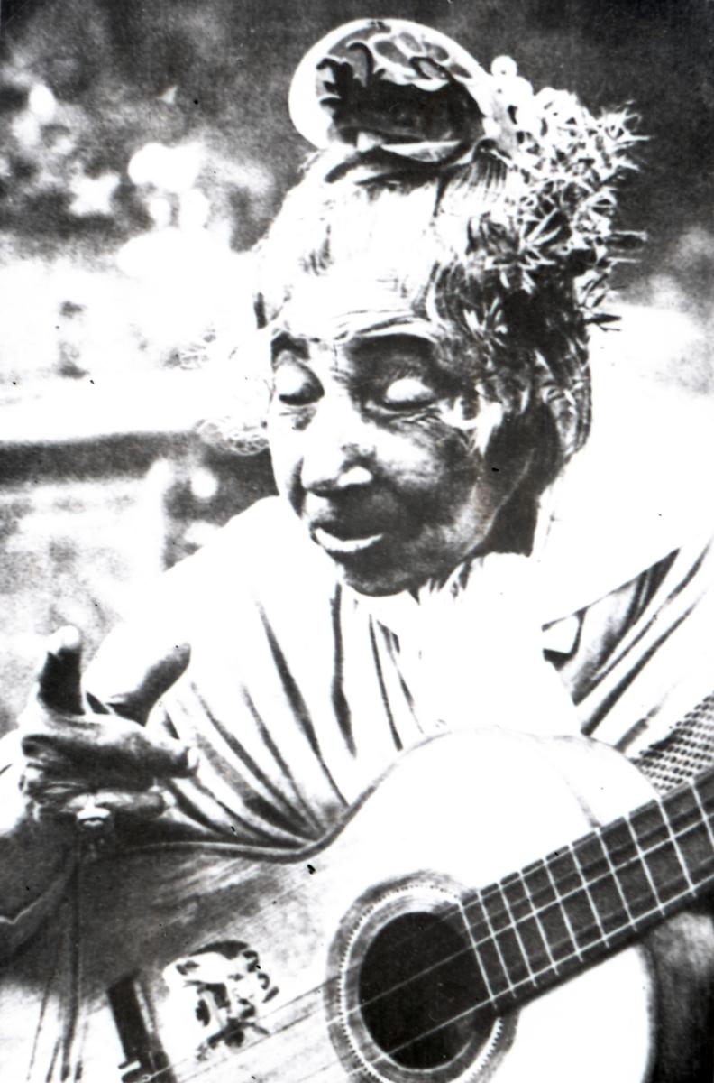 En kvinna poserar för kameran med en gitarr. Bildens ursprung är okänt.