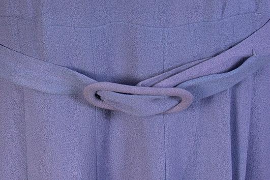 Gråblå, avskuren i midjan. V-ringad hals, draperad krage från axelsömmarna, hoptagen mitt fram. Öppna insyningar mot midjan på ryggstycket. Lång ärm, kraftigt avsmalnande med sprund, axelvaddar. Kjolen i 13 snedskurna våder. Sprund med blixtlås i vänster sida. Skärp med överklätt spänne.  Mått: Livlängd 41 cm, kjollängd 76 cm.