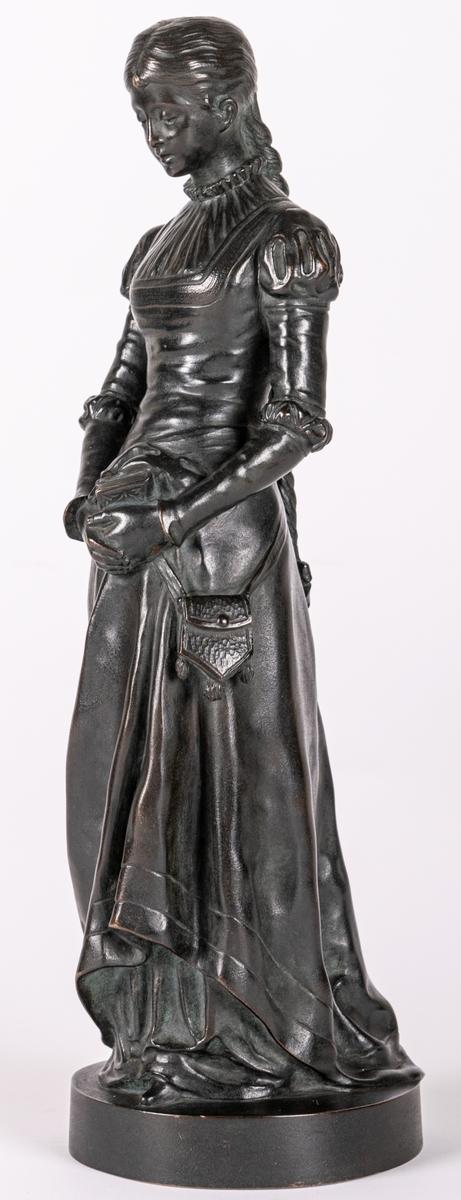 """Statyett av brons, """"Margareta"""", märkt """"Otto Meyer fud"""". Föreställer en ung kvinna med lång fläta. Klänning med puffärmar. Lågt runt postament. Gjuten vid Otto Meyers Konst- Metall- & Zinkgjuteri, grundat 1874 av Otto Meyer, beläget vid Västmannagatan 81 i Vasastan i Stockholm. Otto Meyer var släkt med givaren Waldemar Meyer."""