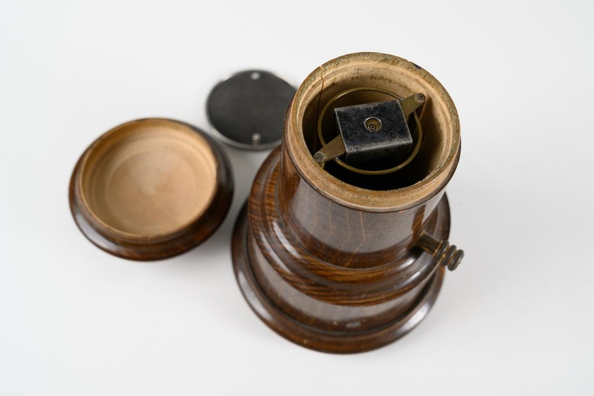Avmagnetiseringsapparat för borttagande av magnetism i klocka. Apparaten består av en rund, svarvad behållare med lock. Under locket finns en bricka av metallnät, där objekt som ska avmagnetiseras placeras. Avmagnetiseringsmekaniken under bricka är av mässing. På sidan av träbehållaren sitter en mässingsskruv som har kontakt med insidans utrustning. Lodrät spricka i träbehållaren.
