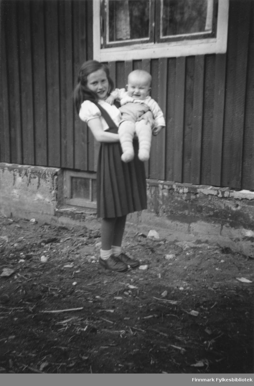 Haldis Aronsen (gift Samuelsen) holder sin lille bror Terje Aronsen i armene utenfor deres hjem i Børselv. Året er rundt 1947.