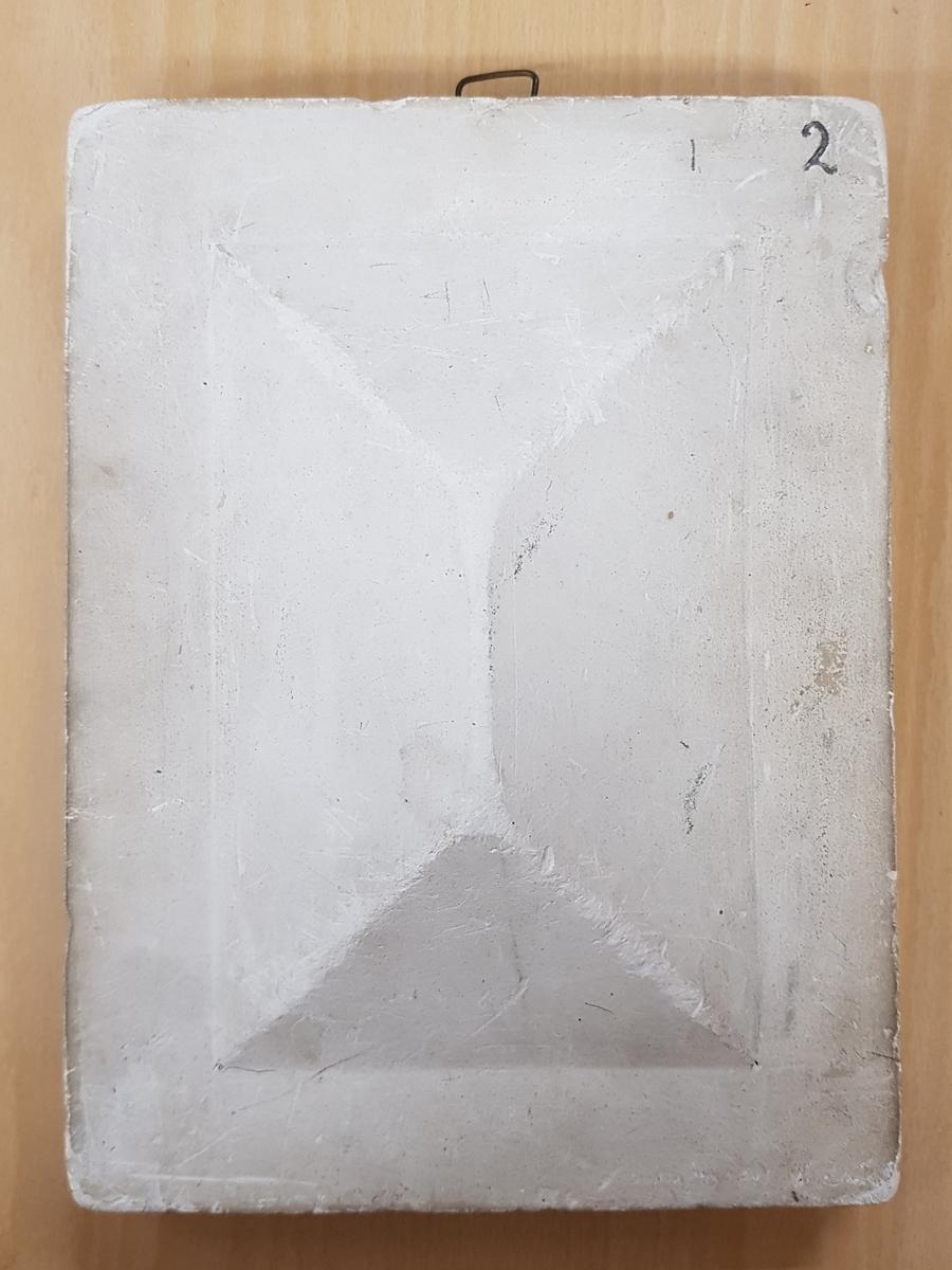 Rektangulär gipsavgjutning med ett mönster i relief.  Ingår i en samling använda i teckningsundervisning för teckning av skuggverkan m.m. Avgjutningarna visar blomsterrankor, druvklasar, blommor, halvklot, valv, kolonnhuvud m.m. Storleken på avgjutningarna varierar från medaljonger med diam. 14,3 cm. till block med storleken 25x38 cm.  Två av avgjutningarna är signerade av olika tillverkare, en av ''Tognarelli Stuttgart'' och en ''Eigenthum von J.F.T. Holmberg Altona''. Avgjutningarna är armerade med trä samt försedda med metallöglor för upphängning. En avgjutning har avslaget hörn och en har en genomgående spricka.  Avgjutningarna upptäcktes i Januari 1995 i källaren på f.d. Vänersborgs Flickskola. De låg packade i en trälåda fylld av träull.