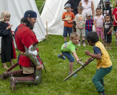 Ridder i middelalderdrakt og delvis rustning kneler mens han instruerer to gutter til å slåss med sverd.