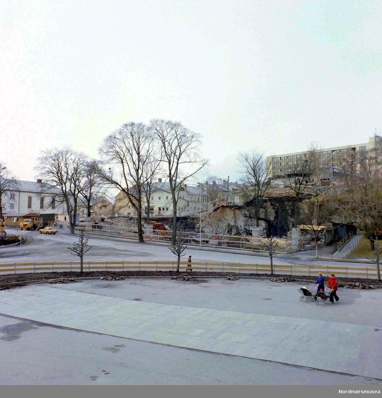Foto sett fra Folkets hus og Kongens plass på Kirkelandet i Kristiansund, hvor vi i bakgrunnen ser pågående arbeid i det som i dag er Sparebank1 Nordvest sin tomt i Langveien 21.  Fotograf er Nils Williams. Fra Nordmøre museums fotosamlinger.