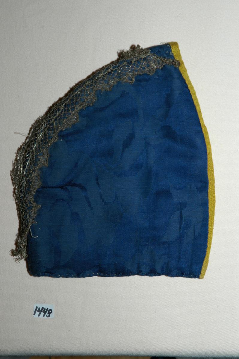 Lue, tobladlue av mørkeblå silkedamask kantet med knallgult silkeband (lerretsvevd). Lua er fôra med linlerret og vattert med stry. Nedrekanten er sydd til med faldesting med grått lingarn. De to delene er sydd sammen med attersting. Sømmonnet er lagt til side og kastet sammen. Kantebandet er vrangsydd på med attersting på retta og faldesting på vranga, 0,5-0,8 cm bredt. Langs sammensyingssømmen er det satt på to rader med en ca. 2 cm brei knipling. Registrering ved Bunad- og folkedraktrådet/Norsk institutt for bunad og folkedrakt v/Jon Fredrik Skauge, 2005, revidert v/Bjørn Sverre Hol Haugen, 2020.