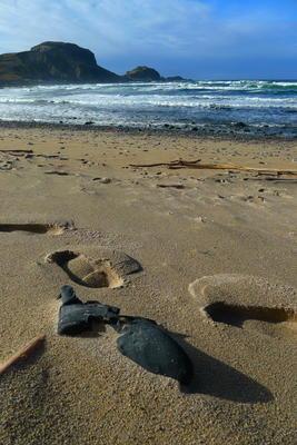 Brun sandstrand med en gammel støve i forgrunnen, hav klippe, blått hav og blå himmel i bakgrunnen.. Foto/Photo