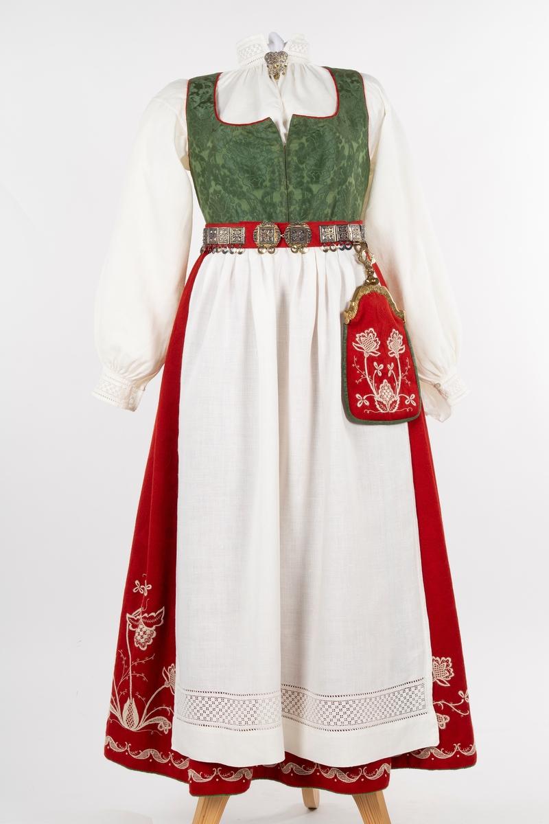 Follo kvinnebunad            Follobunad, kvinne. Foldelagt skjørt med ullbroderi, liv i silkedamask, forkle og skjorte i lin, lue og løslomme. Se FHM. 12081.a-h. Hovedfarge rød eller blågrønn.