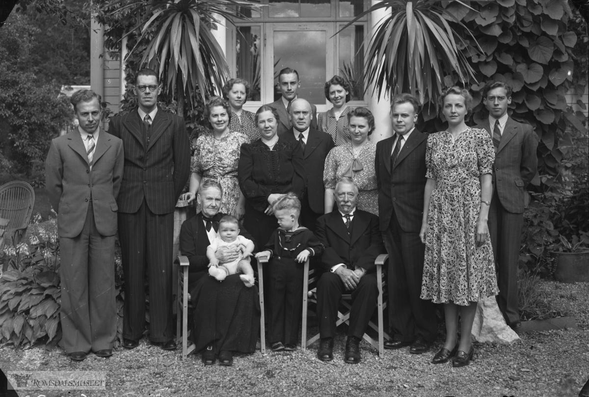 Dette må vere ein Elvsaas-familie. Mannen i møre dress i midten er Nils B. Elvsaas, som var fylkeskasserar. Han som står heilt til høgre er sonen han. Hugsar ikkje namnet. Nr. 2 frå venstre (i mørk stripa dress) må vere Reinholdt Elvsaas som dreiv Sportsfirmaet Elvsaas & Co. Han var morfar til Rudolf Volden, som var den siste disponenten..(serie_n7f8b2)