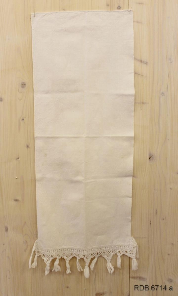 Hjemmevevd og hjemmesydd smalt håndkle i toskaft bomullslerret. Ferdigkjøpt frynsekant påsydd for hånd langs nedre kant og 3 cm oppover langsidene. Jarekant på høyre langside og smal fald sydd ned for hånd på venstre. Øverst i høyre hjørne påsydd hempe av bomullsband. i god stand, lite brukt.