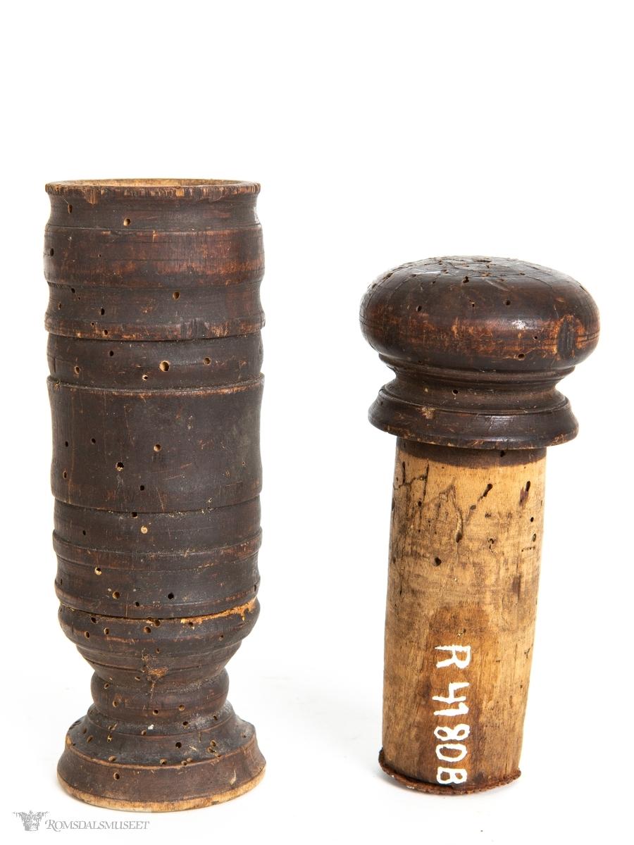 Dreid hylse med liten stett, og pistill med rundt, flatt håndgrep. Jernplate spikret fast i enden av pistillen.
