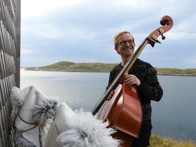 Sigurd Hole poserer med sin kontrabass utenfor en trehus ved vannet, lave fjell i bakgrunnen.. Foto/Photo