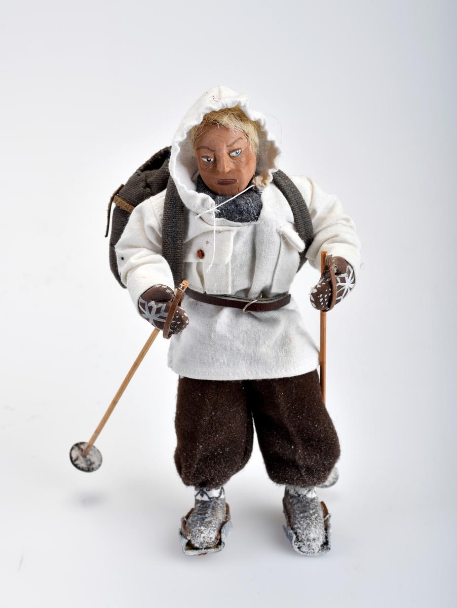 Liten mannsfigur med ryggsekk, ski på beina og skistaver i hendene.