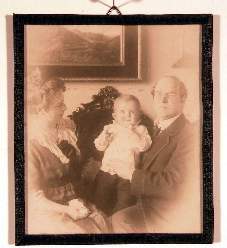 Familiefotografi; foreldrene i sofaen med barnet stående i midten. Far og sønn ser direkte på betrakteren; mor ser på barnet.
