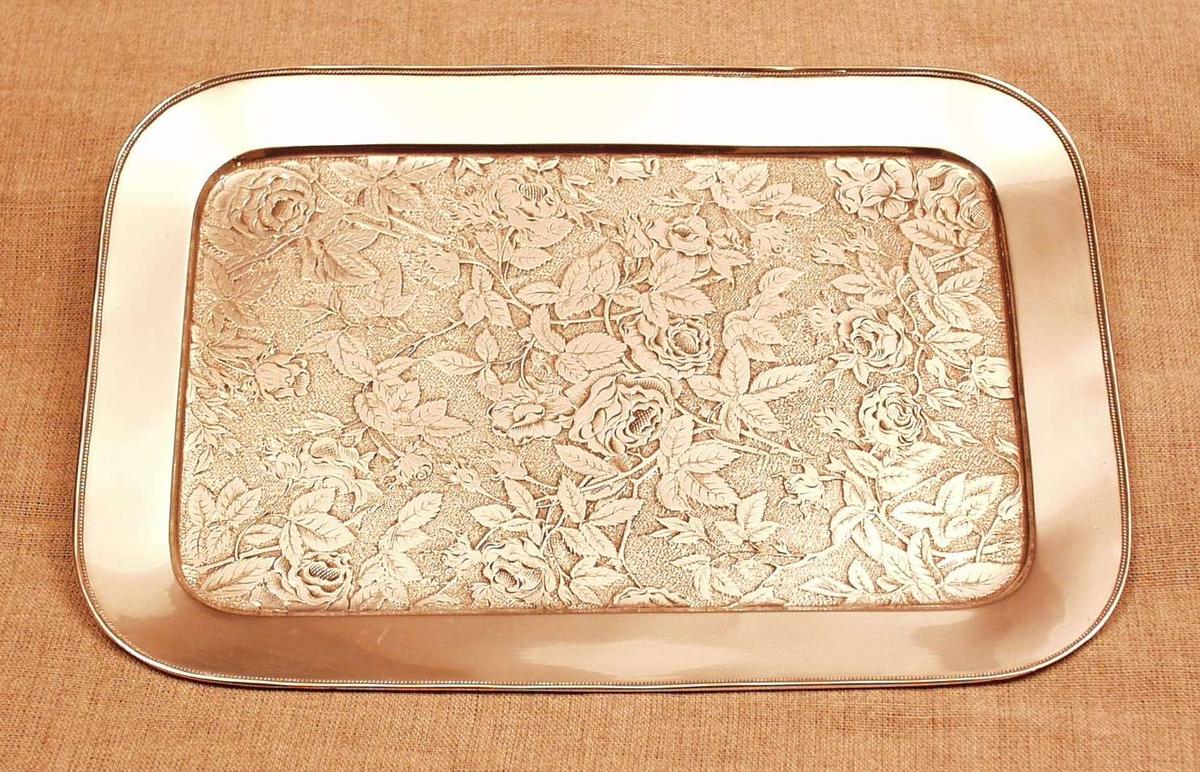 Runde hjørner, utoverbrettet glatt kant med perlekrans. Hamret bunn m. glatt rosemønster i relieff.