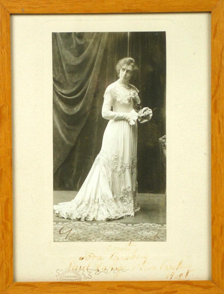 Scenebilde av en ung kvinne i lang lys kjole.