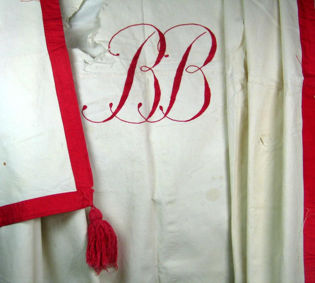 Hvit stor duk med påsydd rød kant og dusker i to hjørner. Rødt brodert monogram i midten.