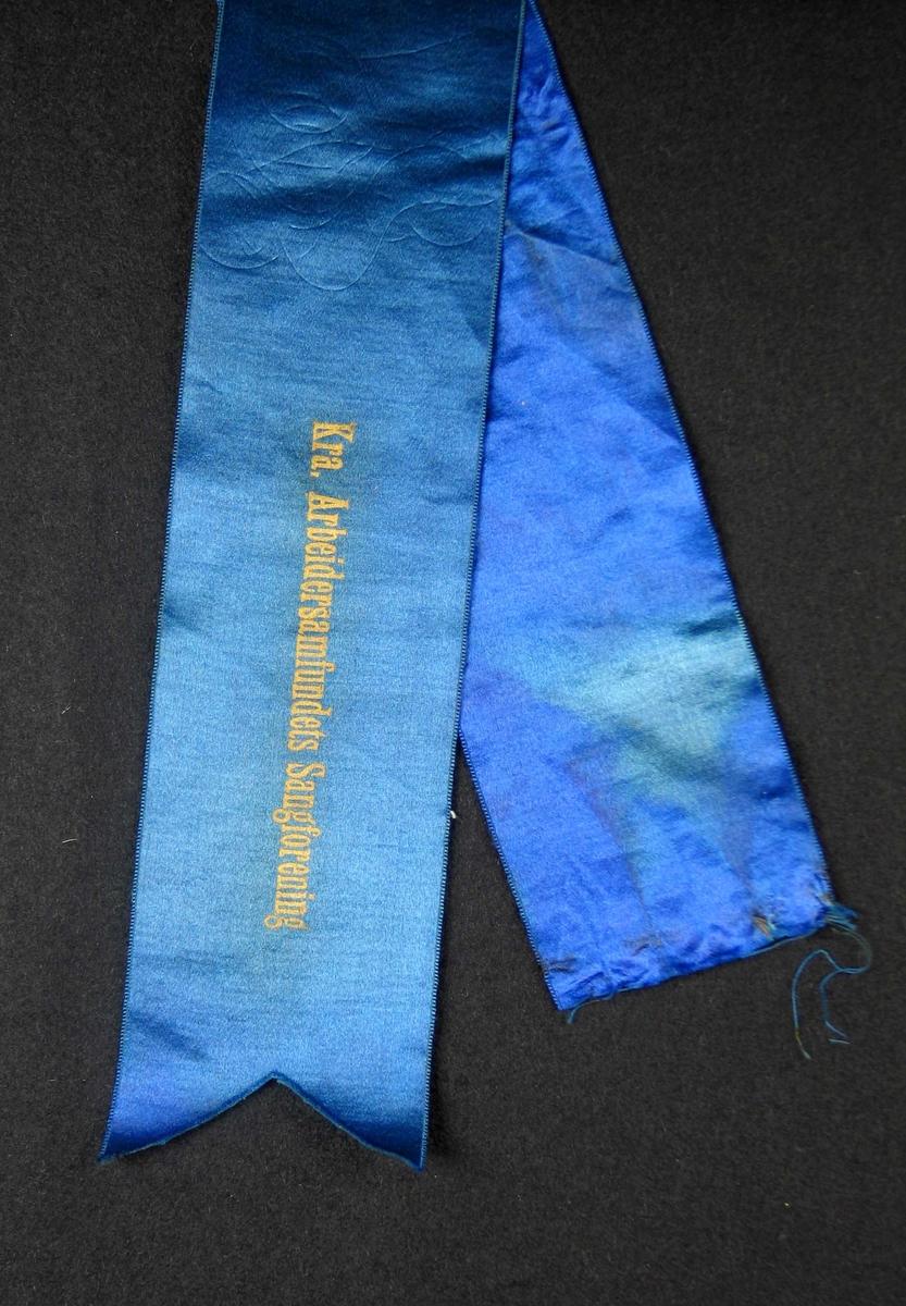 Begravelsessløyfe i blå silke med gullskrift.