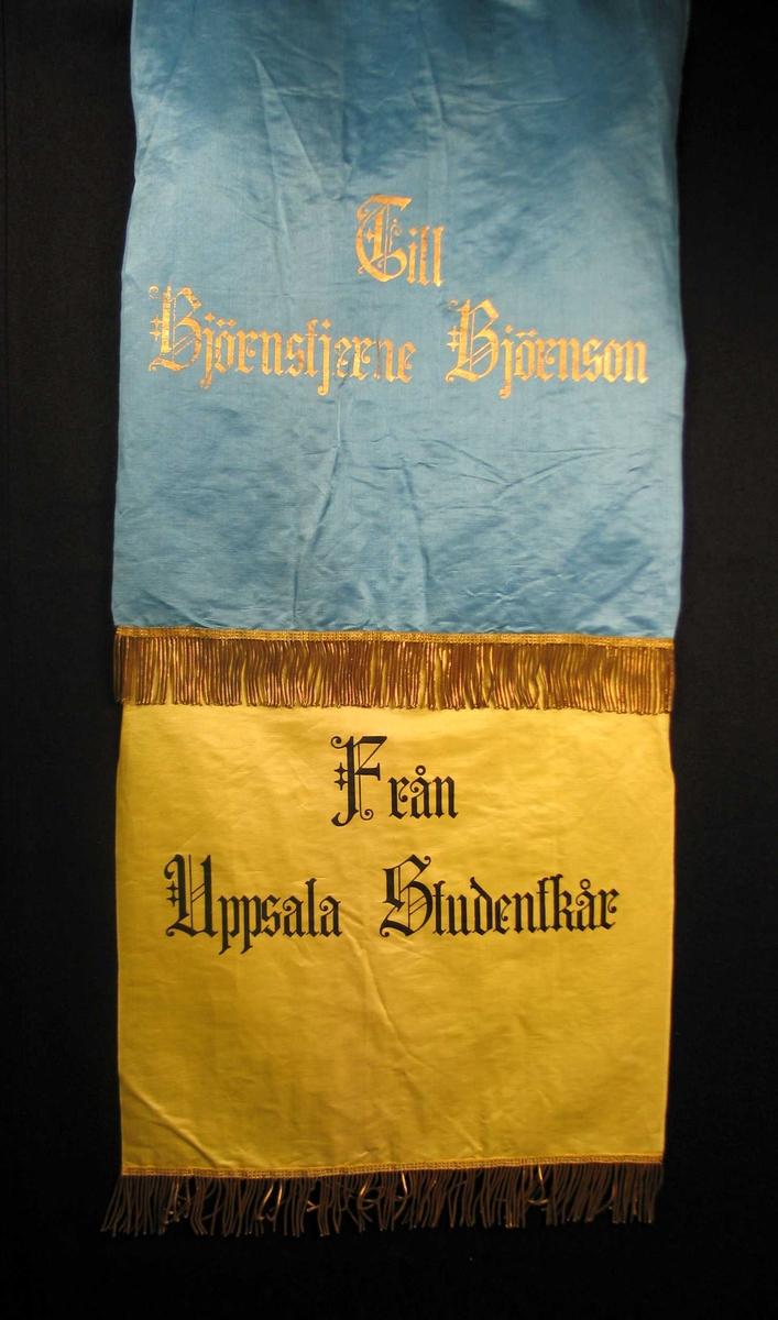 Begravelsessløyfe i blå og gul silke med tekst og frynser i gull.