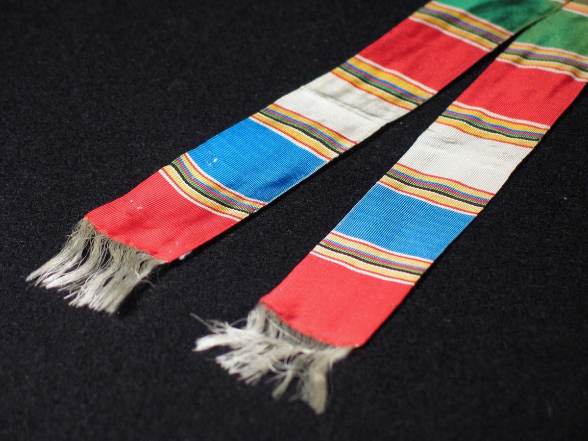 Tverrstripete silkebånd i fargene rødt, blått, hvitt og svart. Båndet har hvite frynser i begge ender som dannes av renningen.