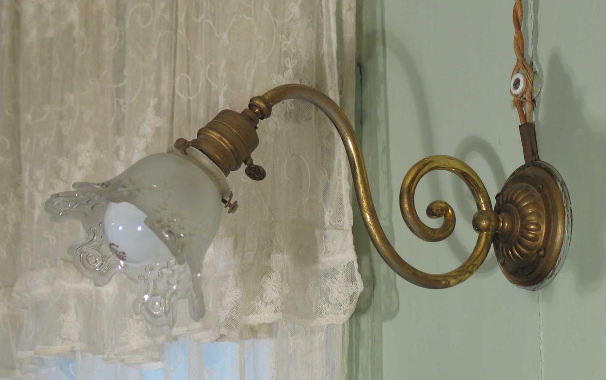 Lampett i messing med s-formet arm og rund sokkel. Frostet glasskjerm med mønstret tungekant.