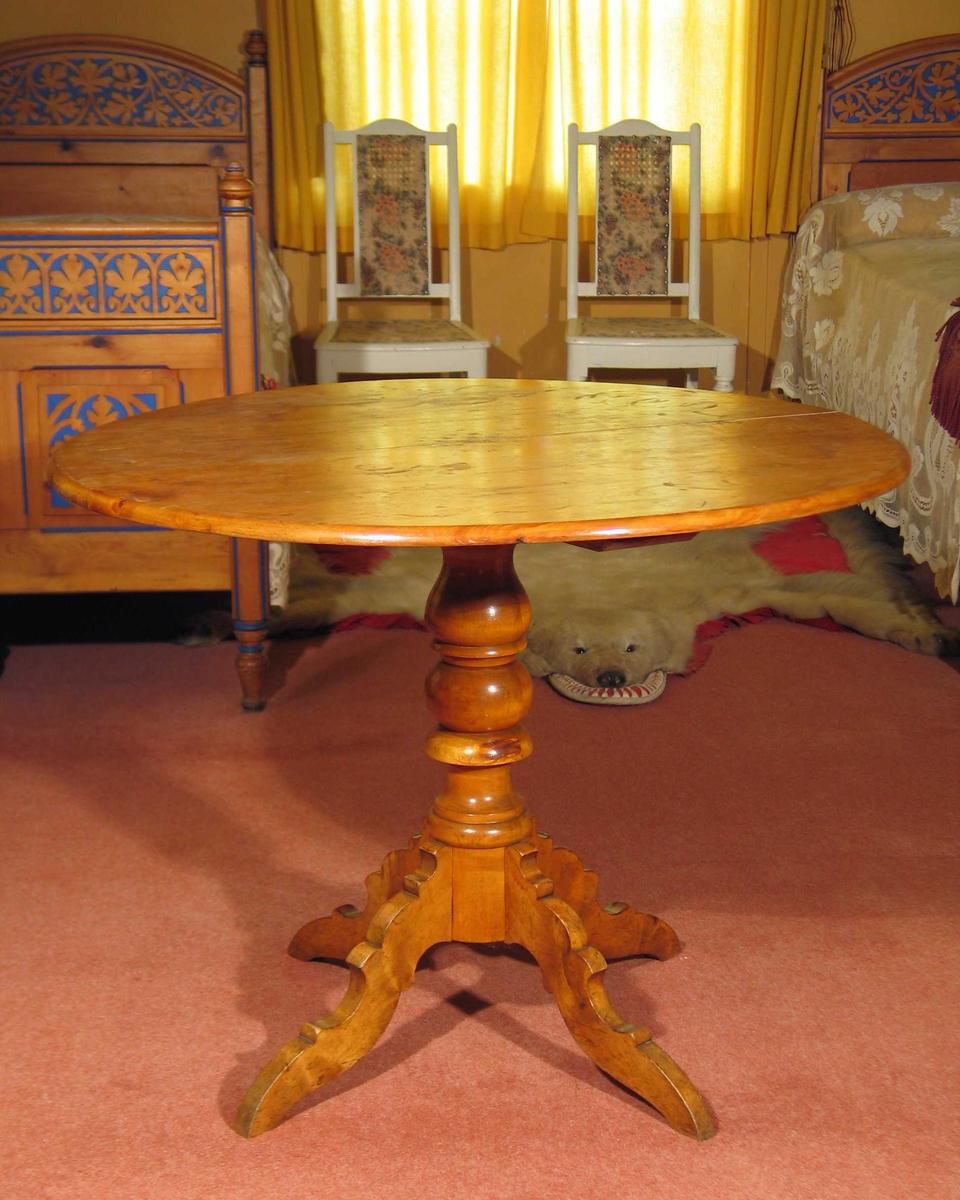 Rundt bord i bjørk med profilert søyle som går ut til fire profilerte ben.