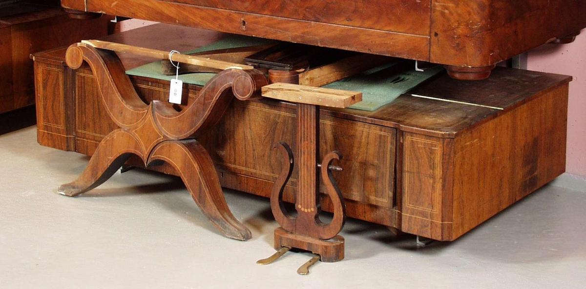 Et taffelpiano i nøttetre som er blitt finért. Langs kantene har det intarsia dekor, i form av smale bånd. Overdelen til taffelpianoet bæres av x-formede sprosser på hver kortside. De x-formede sprossene forbindes med pianoets underdel. Opphenget for pedalene er lyreformet. Omfang: Gg-f4