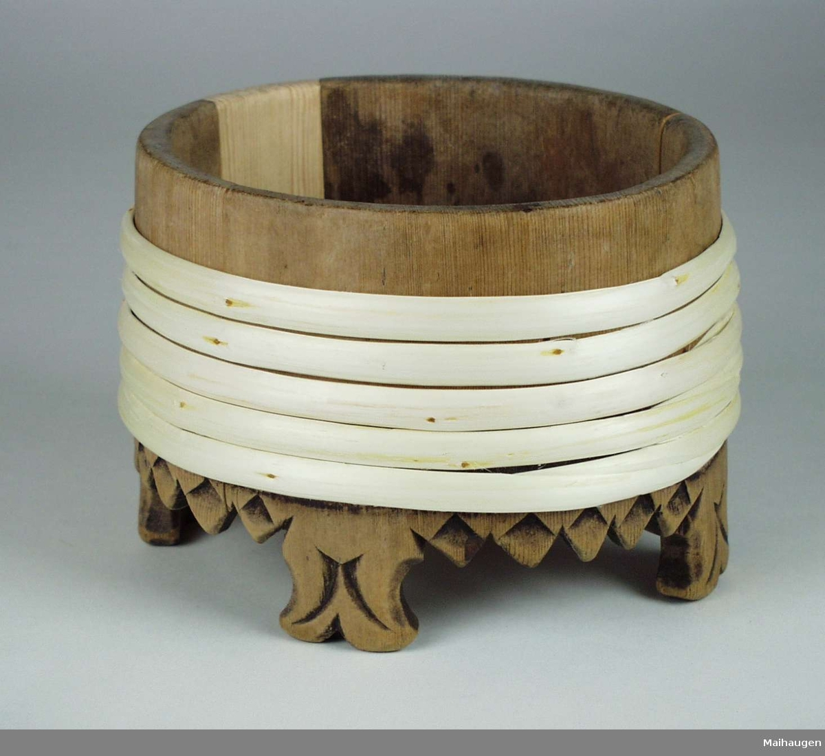 Oval lagget kopp med fire bein og nye gjorder av selje. Tagget kant med enkel utskjært dekor.