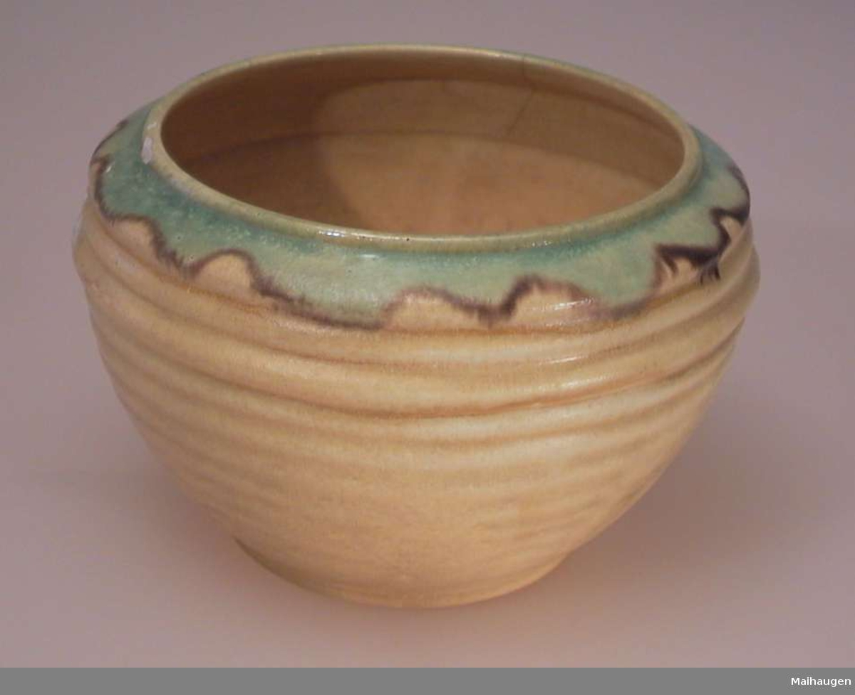 Gul potteskjuler i keramikk med en grønn bord øverst. Riflete mønster vannrett som blir svakere nedover.