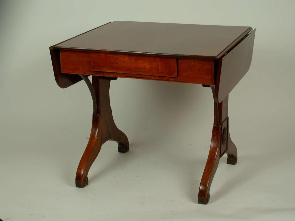 Salongbord med to klaffer og én skuff. Med begge klaffene utslått måler bordet 124,2cm.