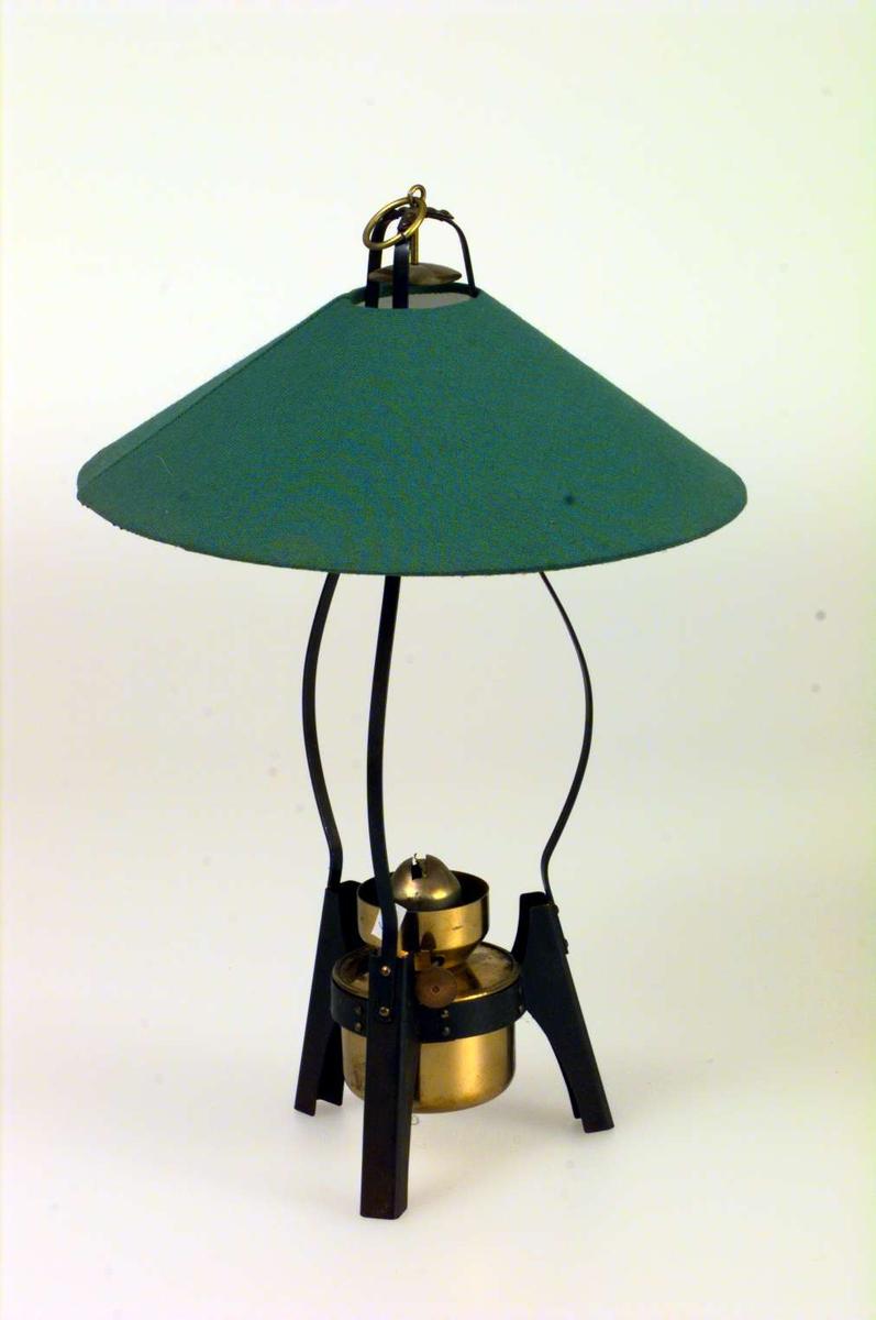 Parafinlampe. Parafinbrenner i messing i et stativ på tre ben. Lampeskjermen er grønn. Glasskolbe mangler.