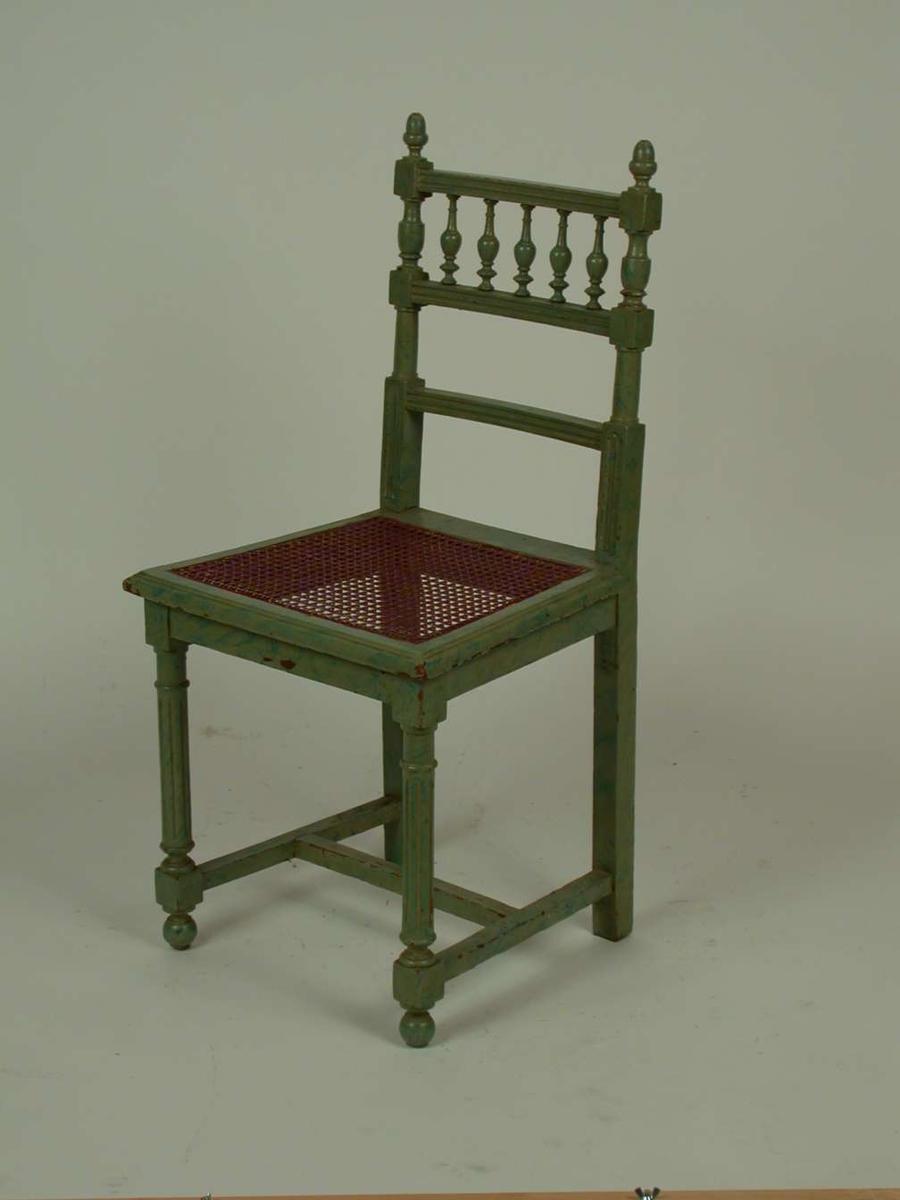 Lasert grønn stol. Setet er av rotting. Den er laget i en blanding av stilarter.