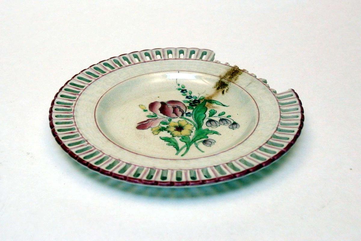 Tallerken i keramikk med kremfarget glasur og med blomsterdekor. Den har 'hullfallskant'. Den er stemplet Demi-porcelaine, Luneville, med bokstavene K og G rundt en krone.Det er slått biter av kanten.