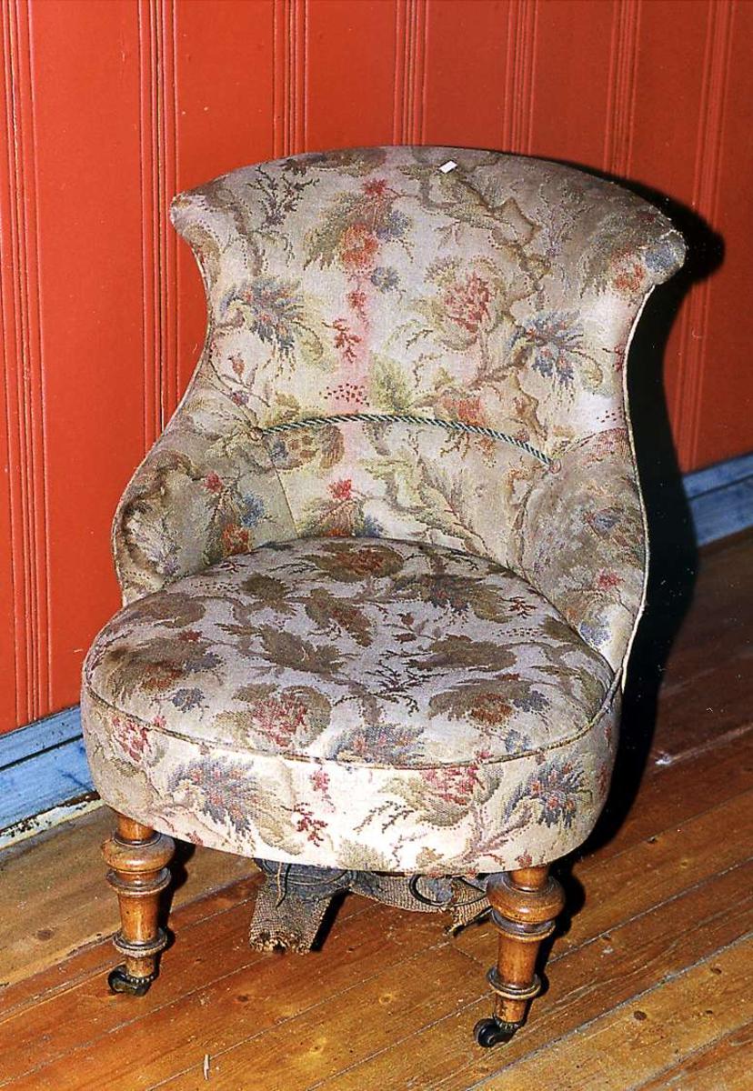 Stoppet stol med mønstret trekk. Stoffet har brunt mønster på grå bunn. Trekket er slitt og flekket. Det er samme trekk som på UB-1027. Stolen har hjul på bena foran.