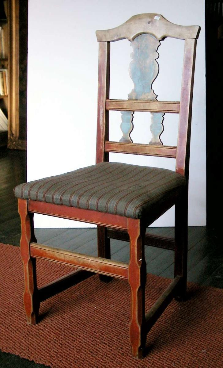 Spisestuestol med pute. Stolen er rød- og blåmalt. Malingen er nedslitt. Trekket er husflidsaktig og har brede grå striper med smale striper i bondeblått, rødt og gult.
