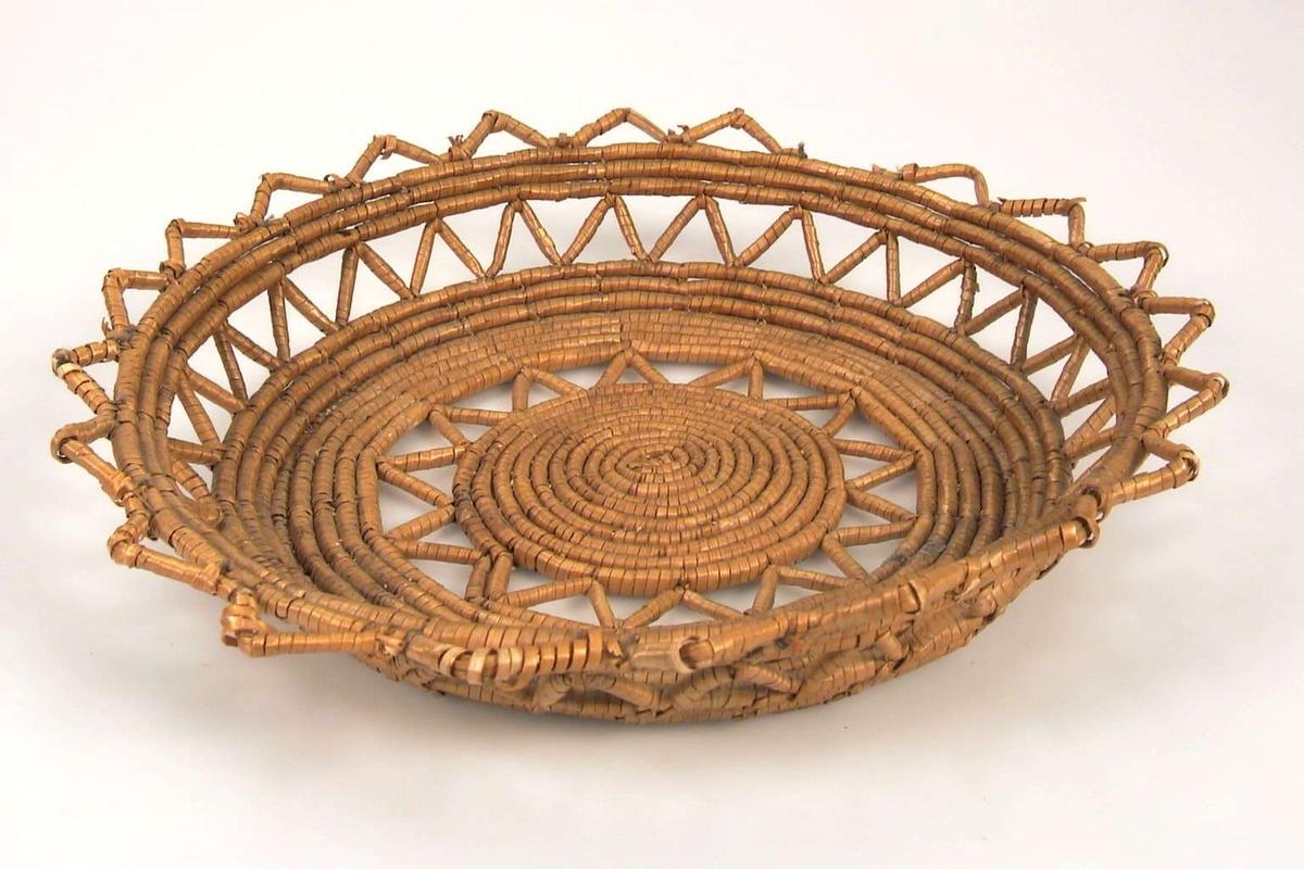 Brødfatet har bunn og sider gjennombrutt med en siksakbord. Fatet er avsluttet øverst med en tungekant.