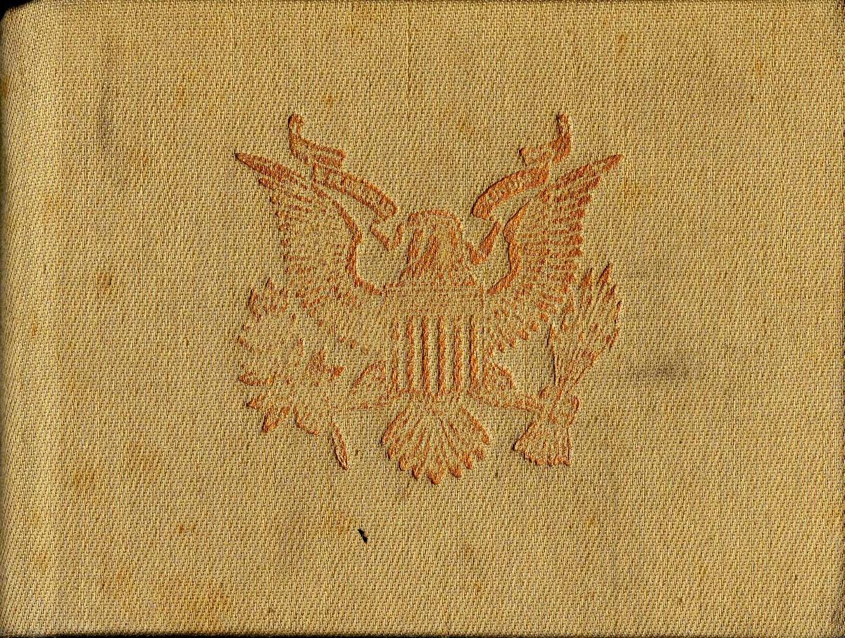 Lite brunt fotoalbum trukket med stoff. Den amerikanske ørnen er trykt på omslaget. Sidene er av svart kartong. Bildene har fotohjørner. Et løst bilde.