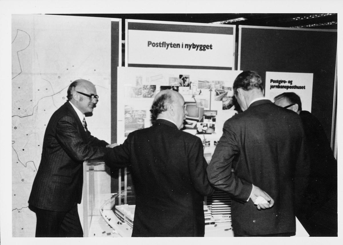 markedsseksjonen, Oslo postgård 50 år, utstilling, modell av postgiro, 4 menn, informasjon