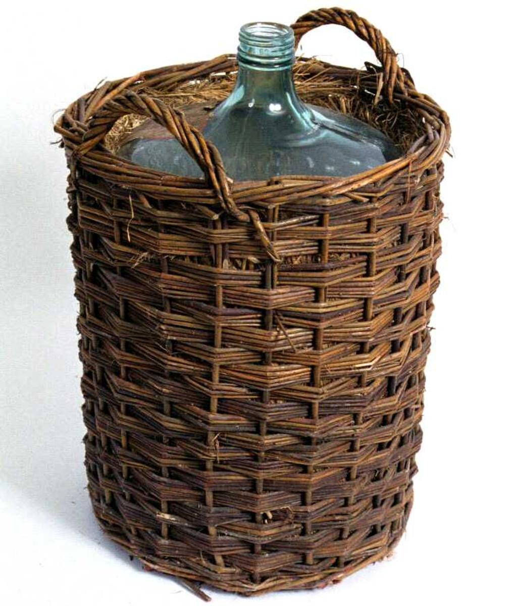 Vinballong av glass, plassert i en kurv flettet av ubarkede pilekvister, utforet m. tvunnet høy. Etikett av jernblikk festet til kurven, etikett av papir klebet til glassballongen.