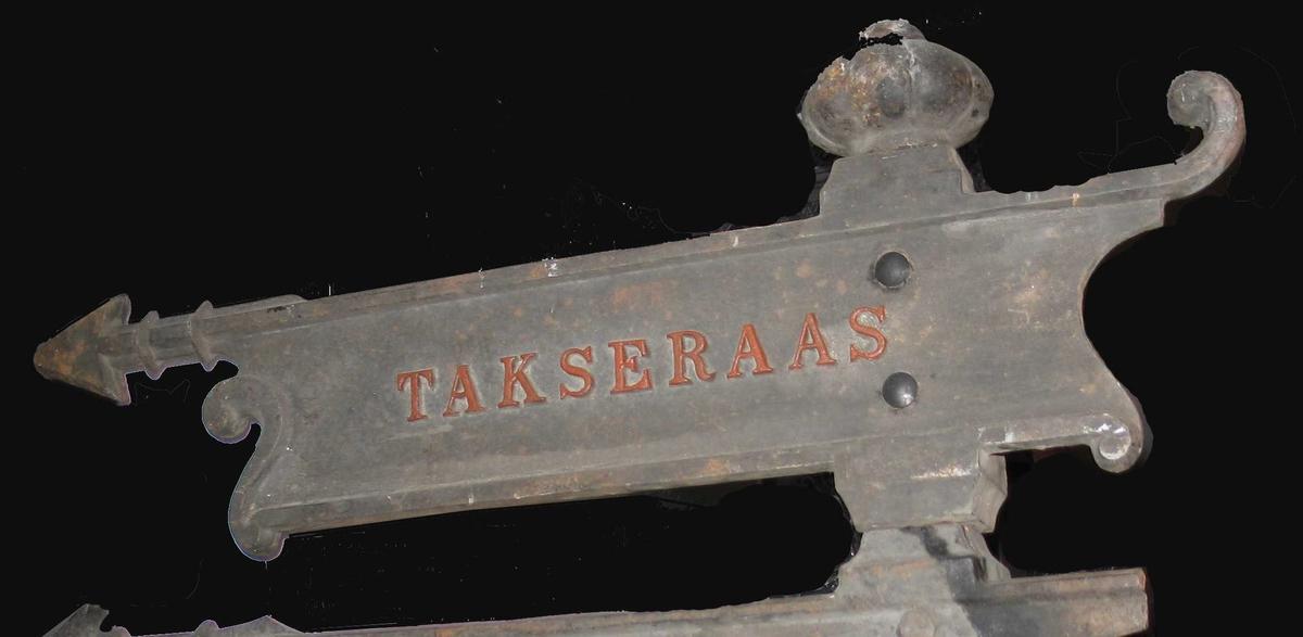 Skilt, komplett, med pil og fjær, - tekst TAKSERAAS - den eneste vi har som er hel, ved siden av VÆRLAND-skiltet.  Er montert på stang med skilt Arendal og Kolbjørnsvik. Nye bolter avslører monteringen.