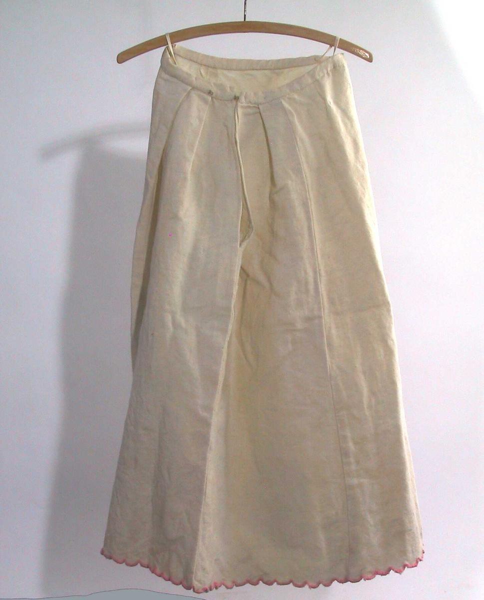 Form: Sammensydd av utskrådde høyder, linning, 2 folder på hver side av åpning midt bak. Lukkes med to hekter i linning. Nedrekant klipt i bølger, sårkant oversydd med rosa ulltråd.